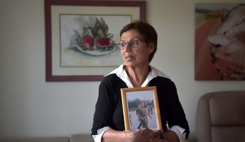 Vered Klein holds a picture of Yaakov Mrvica, a fallen soldier who came to Israel from Serbia in 2002