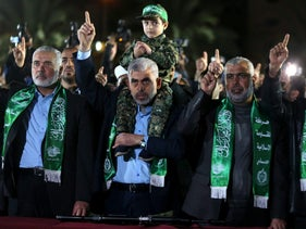 Hamas leader Ismail Haniyeh (R) with the son of senior Hamas militant Mazen Fuqaha, sitting on the shoulders of Hamas Gaza Chief Yehya Al-Sinwar during a memorial service for Fuqaha, in Gaza City March 27, 2017.