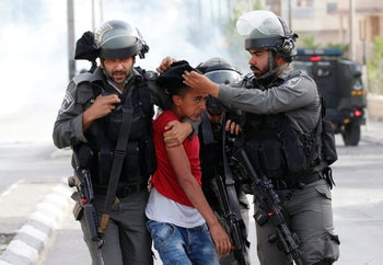 Israeli border policemen detain a Palestinian protester during clashes at a rally in support of prisoners on hunger strike, Bethlehem, West Bank, April 27, 2017.