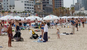 Israelis stand on a beach in Tel Aviv as a two-minute siren is heard in memory of fallen soldiers, May 1, 2017.