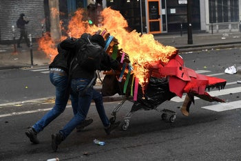 Protesters push a burning trolley towards French CRS anti-riot police officers during a march for the annual May Day workers' rally in Paris on May 1, 2017.