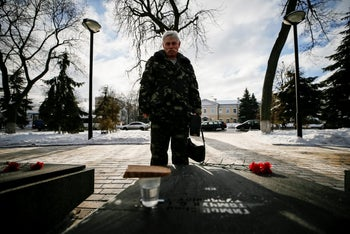 A man stands in front of a monument to servicemen killed during the Soviet campaign in Afghanistan, February 15, 2017.