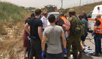 Paramedics treat the woman at the scene of the incident near the West Bank settlement of Tzofim, May 2, 2017.