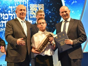 Prime Minister Benjamin Netanyahu and Education Minister Naftali Bennett stand with the contest winner, Sagiv Lugasi, May 2, 2017.