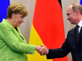 Russian President Vladimir Putin shakes hands with German Chancellor Angela Merkel after a press conference following their meeting at the Bocharov Ruchei state residence in Sochi on May 2, 2017.