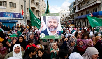 In this file photo, supporters of Hamas hold a picture of Khaled Mashal during a rally to celebrate the militant group's 25th anniversary, in Ramallah, December 2012.