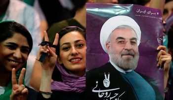 Supporters of Iranian presidential candidate Hassan Rohani hold his portrait during a campaign rally in the capital Tehran on May 4, 2017.