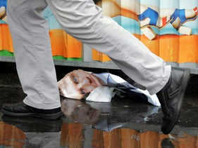 A torn poster of candidate Emmanuel Macron, head of the political movement En Marche !, or Onwards !, for the 2017 French presidential election is reflected in a puddle in Paris, France, May 6, 2017.  REUTERS/Eric Gaillard