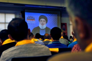 Hezbollah leader Sheikh Hassan Nasrallah speaks on a screen via a video link, during a rally  in a southern suburb of Beirut, Lebanon, Tuesday, May 2, 2017.