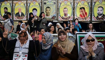 Women demonstrating in front of pictures of jailed Palestinian prisoners in solidarity with Palestinian hunger strikers in Gaza City, May 4, 2017.