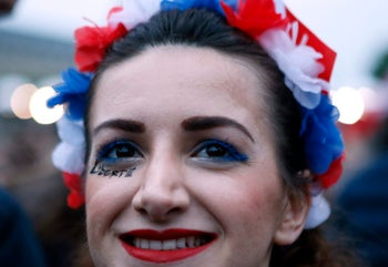 A girl smiles at the Louvre museum where Emmanuel Macron is planning to celebrate, Sunday, May 7, 2017 in Paris. Thousands of supporters of French centrist candidate Emmanuel Macron have let out a big cheer when national television called the presidential election in his favor based on poll projections. (AP Photo/Francois Mori)