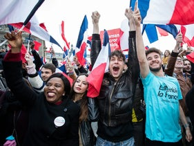 Supporters of Emmanuel Macron wave French flags while reacting as vote projections are announced in the second round of the French presidential election in Paris, May 7, 2017.