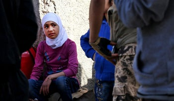 A Syrian girl looks on upon arriving at a staging point in the Barzeh neighbourhood of the capital Damascus on May 8, 2017, as they wait to be evacuated.