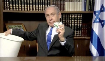 Prime Minister Benjamin Netanyahu crumples and throws the newest Hamas document into the garbage can, in this still shot of his Facebook video.