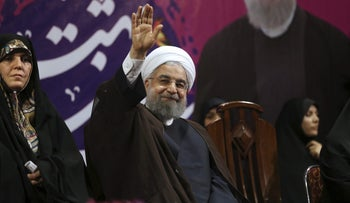 On Tuesday, May 9, 2017, Iranian President Hassan Rouhani, center, waves to his supporters at a campaign rally in Tehran, Iran.