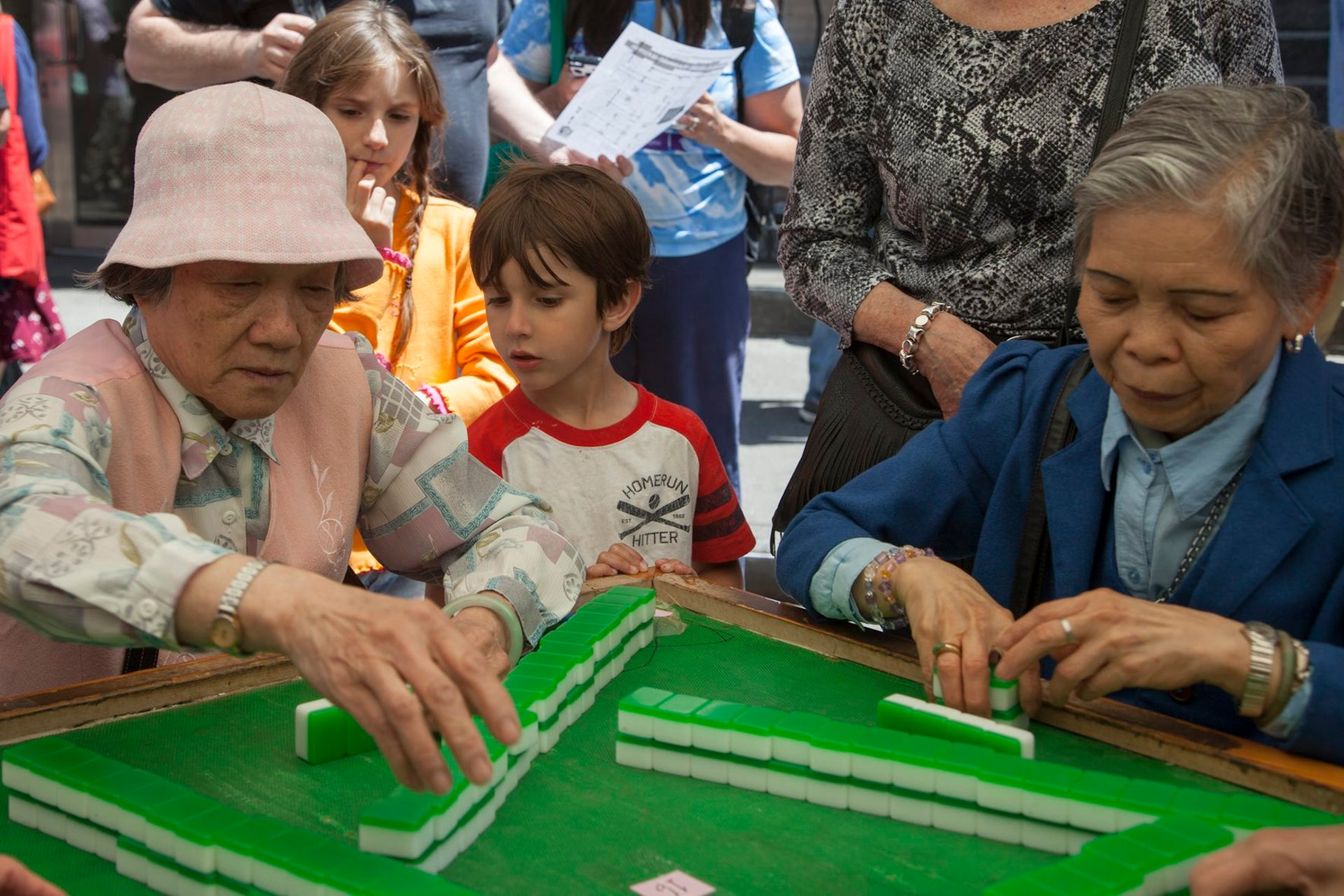 A young boy learning how to play mah-jongg from Chinese-American women.