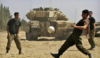 Israeli soldiers play soccer next to a tank at the Kissufim Crossing, on the border with the Gaza Strip, Thursday, June 19, 2008