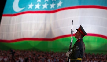 A soldier stands in front of the national flag during an Independence Day celebration in Tashkent August 31, 2012.