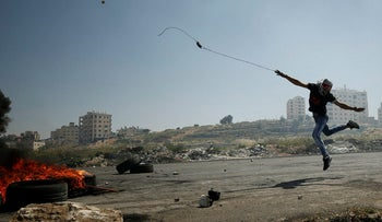 A Palestinian protester uses a sling to hurl stones towards Israeli troops during clashes at a protest in support of Palestinian prisoners on hunger strike in Israeli jails, near the Jewish settlement of Beit El, near the West Bank city of Ramallah May 11, 2017.