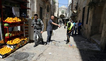 An Israeli border policeman walks by as a worker cleans the floor following an attack in the Old City of Jerusalem May 13, 2017