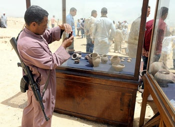 A policeman takes a photograph of objects that were found inside a burial site in Minya, Egypt May 13, 2017.