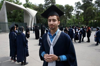 In this Monday, May 8, 2017 photo, Abolfazl Torkamani, 22, a law student, is interviewed by The Associated Press about Iran's upcoming presidential election while wearing his graduation robe and cap for a graduation celebration, at Tehran University, Iran.