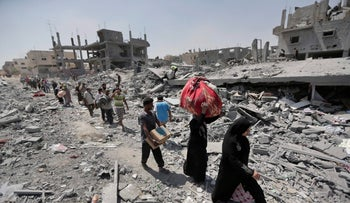 Palestinians carrying their belongings in the heavily bombed town of Beit Hanun, Gaza, Aigust 1, 2014.