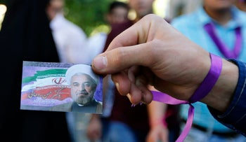 A supporter of Iranian President Rohani distributes brochures in Tehran on May 17, 2017.