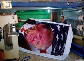 Palestinians print a poster depicting U.S. President Donald Trump in preparations for his planned visit, in the West Bank town of Bethlehem May 21, 2017.