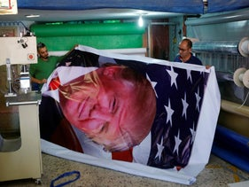 Palestinians print a poster depicting U.S. President Donald Trump in preparations for his visit to Bethlehem, May 21, 2017.
