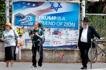 Israelis walks past a poster welcoming and supporting US President Donald Trump in downtown Jerusalem, on May 21, 2017, on the eve of a two-day visit of the US president. US President Donald Trump heads for Israel and the Palestinian territories on May 22 as part of his first trip abroad since taking office, hoping to renew peace efforts but with controversy trailing him. / AFP PHOTO / MENAHEM KAHANA