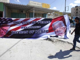 Palestinian men hold a banner bearing a portrait of U.S. President Donald Trump and Palestinian President Mahmoud Abbas at a printer's in Bethlehem, May 21, 2017.