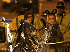 Two women wrapped in thermal blankets stand near the Manchester Arena, where Ariana Grande had been performing, after a deadly attack, Manchester, U.K., May 23, 2017.