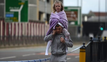 A man carries a young girl on his shoulders away from Britain's deadliest terror attack in over a decade in Manchester. May 23, 2017.
