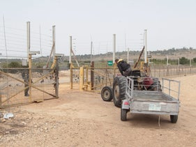 A Palestinian drives into his land beyond the West Bank separation barrier near Qalqilya, last month