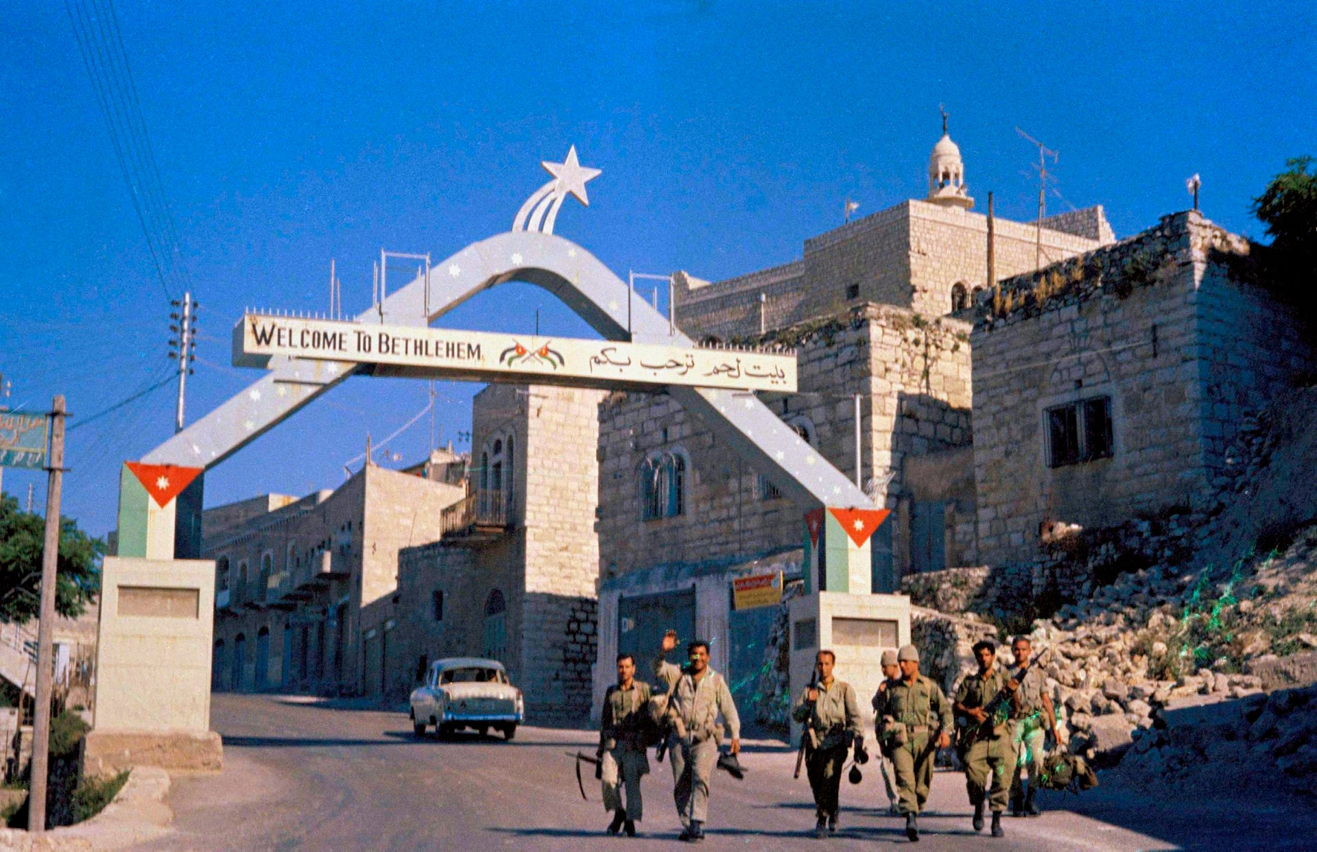 """Israeli troops walking by a decorative """"Welcome to Bethlehem"""" arch, June 9, 1967."""