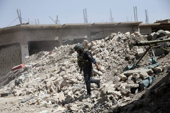 A member of the Iraqi Federal Police walking over debris at the frontline in western Mosul, Iraq, May 29, 2017.
