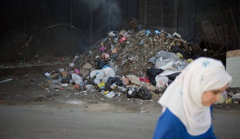 a Palestinian woman walking past garbage along a section of the separation barrier in Shoafat refugee camp, East Jerusalem, May 17, 2017.