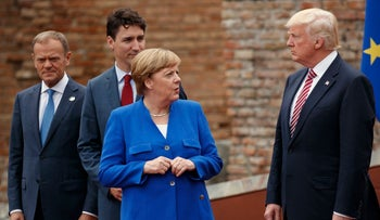 German Chancellor Angela Merkel talks with U.S. President Donald Trump during a family photo with G7 leaders in Taormina, during the G7 Summit, May 26, 2017.