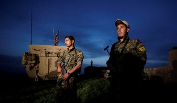 File photo: Kurdish fighters from the People's Protection Units (YPG) stand near a U.S military vehicle in the town of Darbasiya near the Turkish border, Syria April 28, 2017.