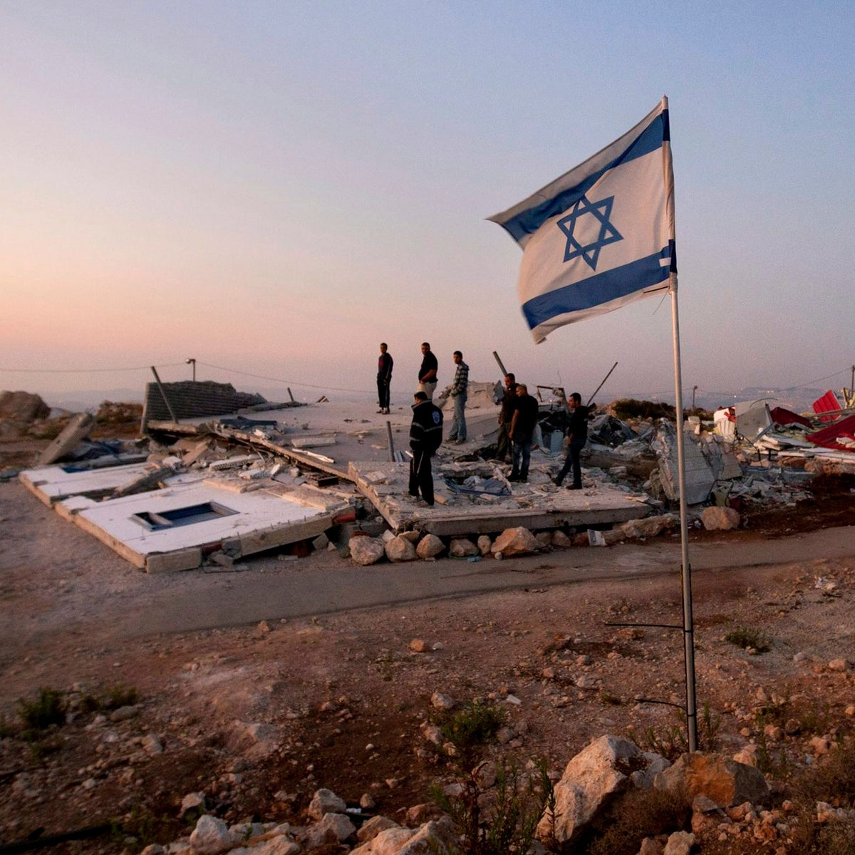 In this Sept. 5, 2011 file photo, Jewish settlers stand on the rubble of a house demolished by the Israeli authorities in the West Bank settlement of Migron.