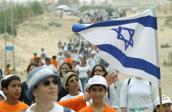Demonstrators carry flags as thousands of Israelis rally in the Gush Katif settlement bloc in the Gaza Strip, April 27, 2004, to protest Prime Minister Ariel Sharon's plan to abandon Jewish enclaves in the Gaza Strip.