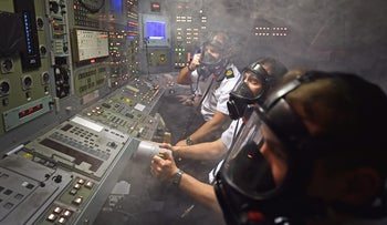 Royal Navy personnel respond to a fire in a control room of a Vanguard Class ship simulator at Her Majesty's Naval Base, Clyde in Rhu, Scotland on January 20, 2016.