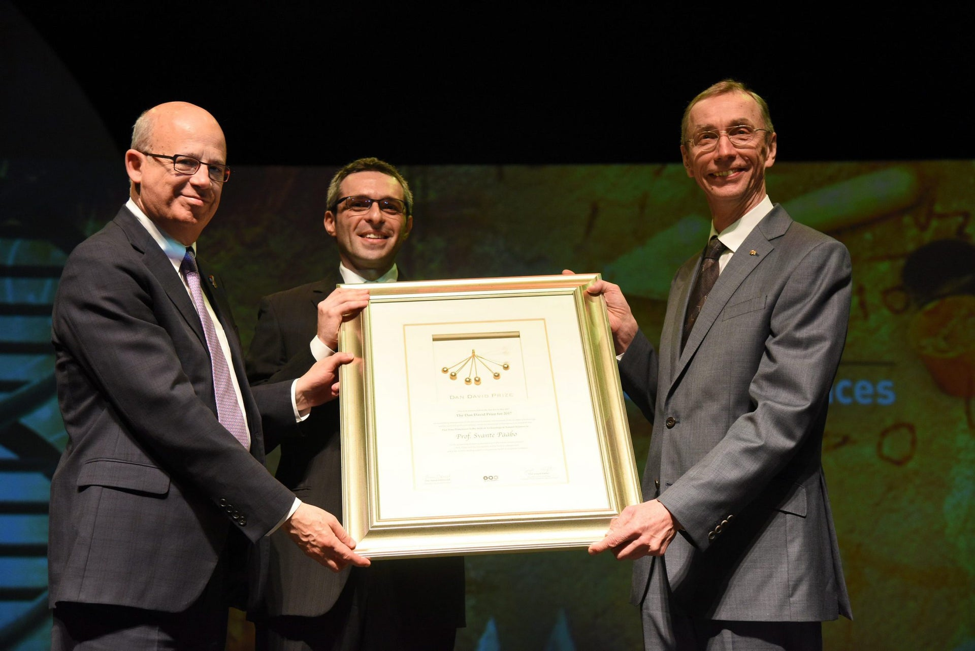 Prof. Svante Paabo, right, receiving the Dan David prize from Prof. Joseph Klafter, left, and Ariel David.