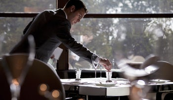 A restaurant manager examines a table arrangement in the River Restaurant at the Savoy hotel in London.