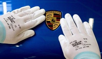 A worker places the final touches on a Porsche logo.