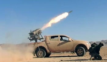 Syrian government troops firing rockets at insurgents in Homs province, May 25, 2017.