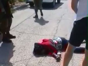 Image from video showing Israeli cursing wounded Palestinian assailant as she writhes in pain on ground
