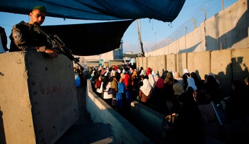 Palestinians wait to cross the Qalandiyah checkpoint between the West Bank city of Ramallah and Jerusalem, June 2, 2017.