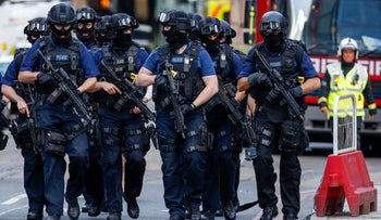 Armed police officers patrol streets near the scene of a terror attack in London, U.K., on June 4, 2017.